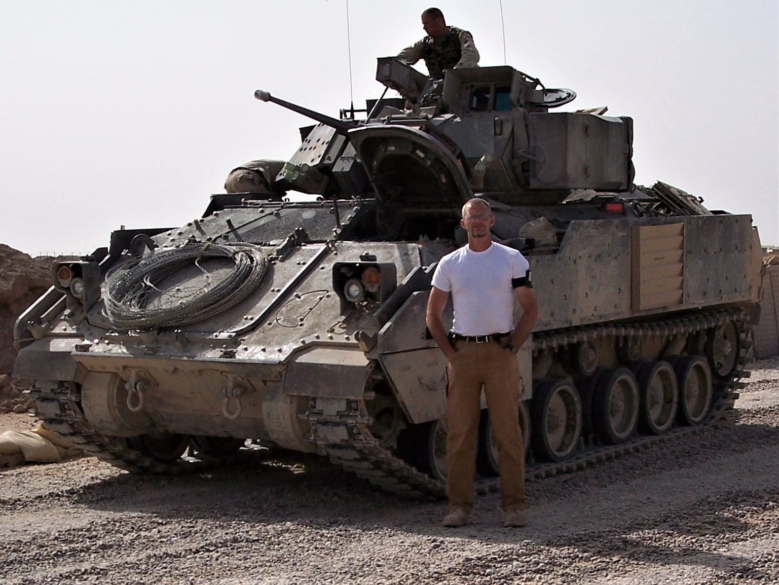 Paul Barnard stands in front of a tank at a military base.