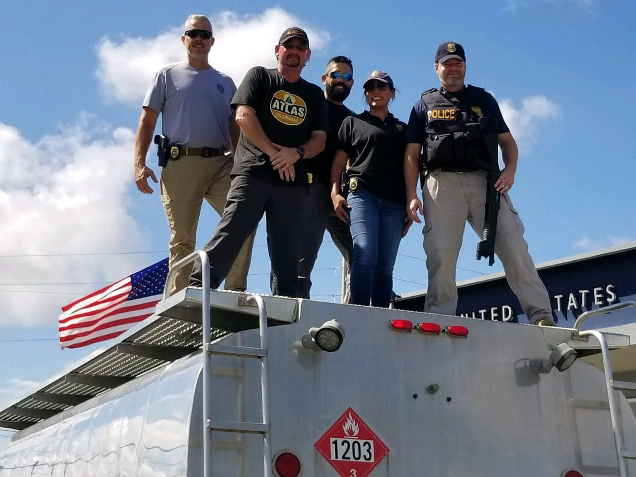 Atlas drivers stand with Puerto Rican police officers on top of an Atlas tanker.
